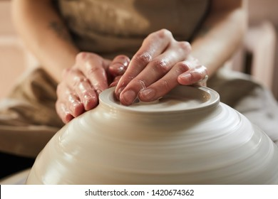 Extreme closeup of unrecognizable female artisan shaping bowl on potters wheel, copy space