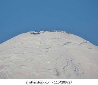 Extreme closeup of the very top of snow covered Mount Rainier isolated below a clear blue sky on a summer day at Mount Rainier National Park in WA state. Several mountain crevasses can be seen.