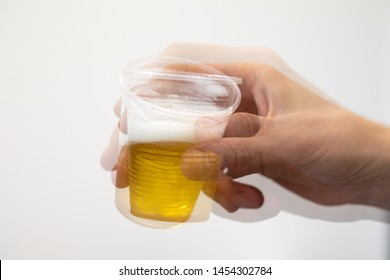 An extreme close-up view on the shaking hand of a man holding a beaker filled with lager. Man tries to enjoy drink with onset of Parkinson's disease.