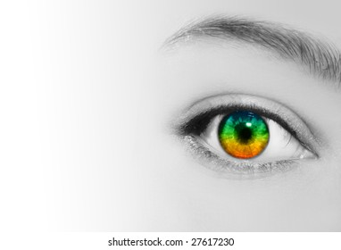 An extreme closeup of a woman's eye which is in rainbow colors and her skin is in black and white.