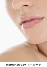 Extreme closeup of a young woman wearing pink lipstick against white background