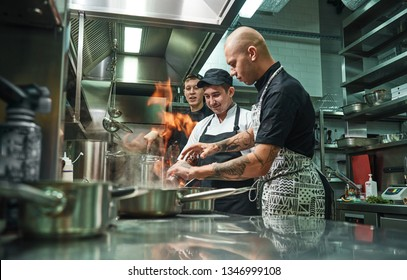Extreme cooking. Profesional chef teaching his two young trainees how how to flambe food safely. Restaurant kitchen