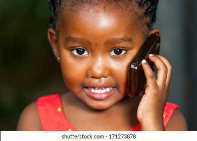 Extreme facial portrait of cute african girl having conversation on smart phone.