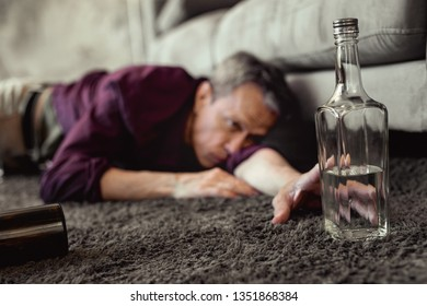 Extreme form. Desperate pity adult man reaching out for half-empty bottle of vodka while mindlessly lying on floor