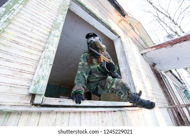 Extreme girl with paintball marker jumping from open window