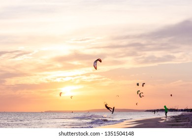 extreme group of professional kiters slide waves, jumps air on black sea with sail wing in hands led wind an sunset, onlookers photographers seagull on shore. village of annunciation. backlit, toned