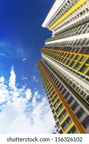 An extreme low angle shot of a new colorful high rise apartment against the sky.