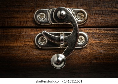 An extreme macro shot of an antique sliding metal clasp that securely latches a polished wooden box.