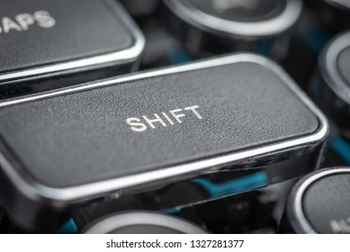 An extreme macro shot with shallow depth of field and selective focus on the SHIFT key in a black and silver vintage-inspired clicky typewriter keyboard.