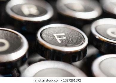 An extreme macro shot with shallow depth of field and selective focus on the capital letter F key in a black and silver vintage-inspired clicky typewriter keyboard.