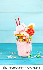 Extreme milkshake. Freakshake. Pink strawberry freakshake with sweets on blue background. Selective focus. Overshake