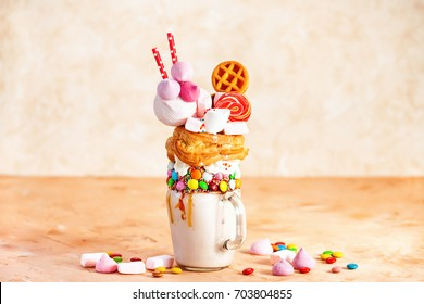 Extreme milkshake. Overshake. Freakshake. Pink strawberry freakshake with sweets on the table. Selective focus.