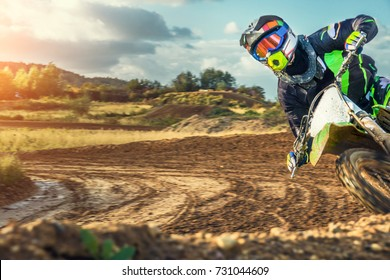 Extreme Motocross MX Rider riding on dirt track on a sunny late summer day