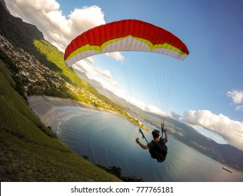 extreme paraglider pilot over the beach