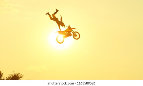 Extreme pro motocross rider riding fmx motorbike, jumping huge jump performing dangerous stunt against the sky. Professional motocross biker jumps big air trick over golden sunset sun