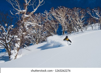 Extreme pro skier shredding the deep powder snow in the sunny Japanese mountains. Cool shot of an active male tourist skiing off piste and carving down the untouched mountain. Awesome winter sport.