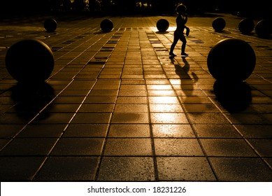 Extreme silhouette of child at play in public park on wet pavement, Weber Point in Stockton California