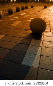 Extreme silhouette of granite spheres in public park with wet pavement at Weber Point in Stockton California
