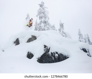 Extreme Snowboarder Jumping Off Powder Cliff Holding Grab in Backcountry
