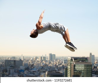 extreme sport, parkour and people concept - young man jumping high over tokyo city background