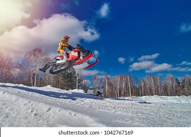 Extreme sport race snowmobiles. Snowmobile in high jump above track. Sportsman on snowmobile. Winter competition, sunny day. Trick against blue sky. Snow motor sports Copy space.
