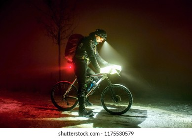 Extreme Sport race.Winter Enduro Biking challenge. Biker check possition in map. Lost way under fresh snow. Winter misty night  with snow.