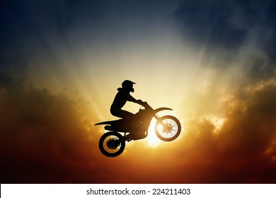 Extreme sports background - silhouette of biker jumping on motorbike on sunset