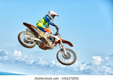 Extreme sports, motorcycle jumping. Motorcyclist makes an extreme jump against the sky.