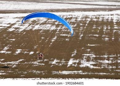 Un pilote sportif extrême volant avec un moteur paramoteur et un parapente se prépare à atterrir sur la piste ulm
