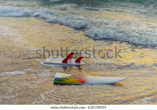 Extreme sports surfing on waves in the ocean. The surfer fell from the board and broke it against the waves. Broken two-piece surfboard. Short board for dynamic skating on waves.