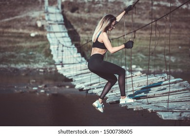 Extreme sport.Young beautiful sportive girl. Girl is exercising. Outdoor sport. Beautiful strong sexy athletic caucasian fitness woman. Woman fitness outdoor concept