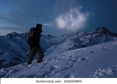 Extreme tourism. Brave expeditor lights the way with a headlamp at night winter mountains. Man with backpack commit climb on snowy slope in high ridge. Ski tour