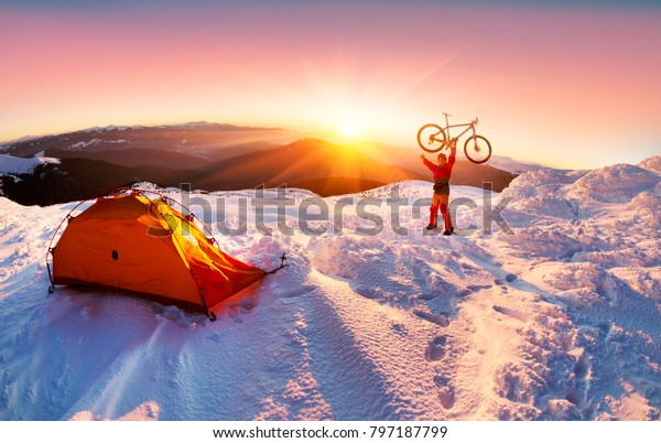 extreme unique winter ascent of the rider to the highest peak of Ukraine in Eastern Europe in a  frost with a professional mountain bike in the background of a picturesque landscape