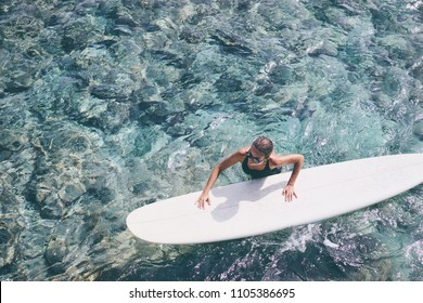 Extreme Water Sport. Surfing. Healthy Athletic Young Surfer Girl Holding Surf Board While Standing In Clear Water, Top View. Summer Vacation. Lifestyle. Leisure, Hobby, Wellness, Fitness.