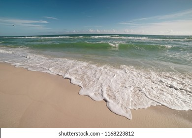Extreme wide-angle scenic at Pensacola Beach in Florida. Seagulls, breakers, blue skies, emerald waters