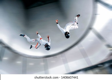 Extreme wind. Levitation in wind tunnel. Indoor sky diving. Team flyers. Yoga fly in wind tunnel. Indoor skydiving sports.