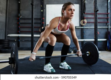 Extreme workout: muscular female athlete starting barbell exercise standing in squat stance