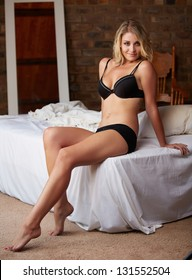 Extremely beautiful and sexy young adult caucasian woman with honey blonde hair wearing lingerie in a boudoir bedroom setting in various poses