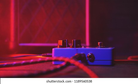 Extremely close up of button for effect electro guitar pedal. Red neon light in night club during show concert