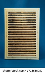 Extremely dirty and dusty white plastic ventilation grill for the home on a blue background. Hygiene.
