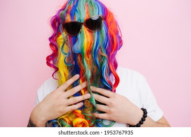 Extremely funny looking man in a wig over face, worn back to front and sunglasses over it. He is touching beard resembling hair. Over pink background.
