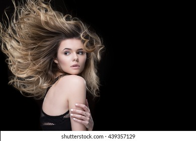 Extremely gorgeous. Stunning young woman embracing herself looking over her shoulder with her hair swept by wind on black background copyspace on the side