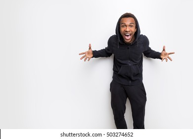 Extremely happy African American man making a crazy face against white wall. Concept of a weirdo. Mock up