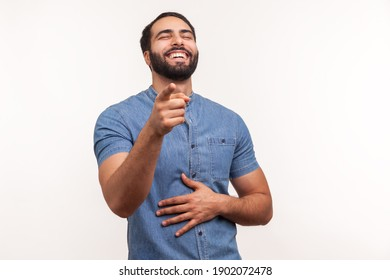 Extremely happy bearded man laughing holding hand on belly and pointing finger at you looking at camera, funny ridiculous joke. Indoor studio shot isolated on white background