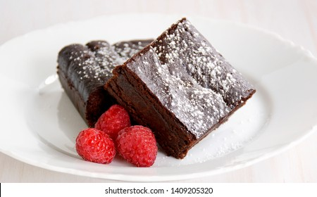 Extremely rich fudgy chocolate brownies made without any grains, totally gluten free. with raspberries.