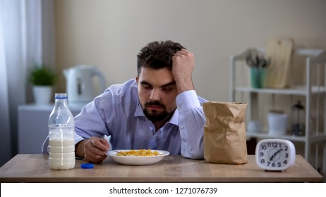 Extremely tired young bachelor sleeping over plate with corn flakes avitaminosis