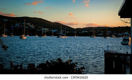 Extremely vibrant and colorful sunrise in the docks of the tropical Caribbean island of Culebra Puerto Rico with many small sail boats for fisherman and tourists.