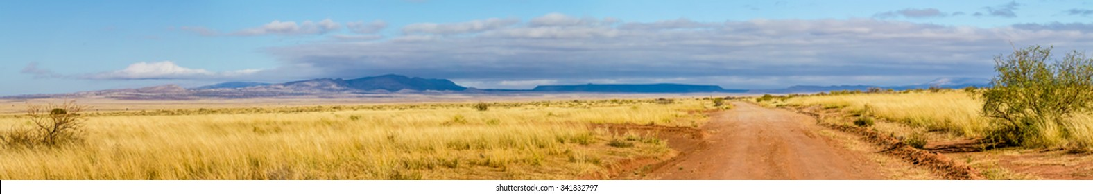 An Extremely Wide High Resolution Panoramic View of an Old Dirt Road Heading Out into the Desert of New Mexico Towards a Northern Mountain Range.