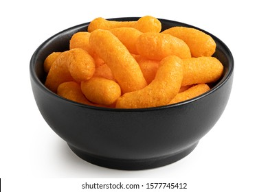 Extruded cheese puffs in a black ceramic bowl isolated on white.