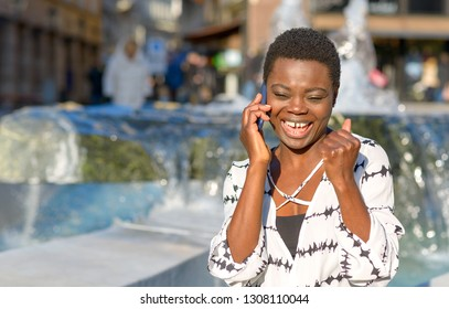 Exuberant young African woman laughing on her mobile phone as she stands in front of a city fountain chatting to a friend